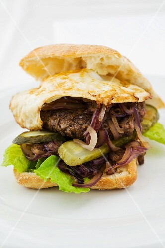 An elk burger on a ciabatta roll with fried red onion, gherkins, lettuce and a fried egg