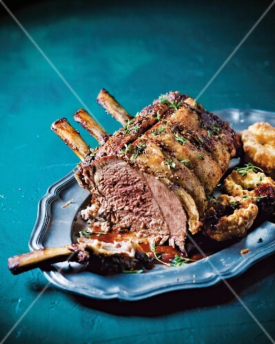 Rack of beef with herbs, Yorkshire pudding and horseradish gravy on a serving platter