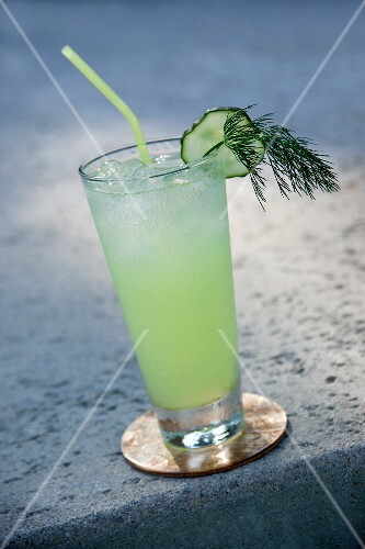 A cucumber cocktail garnished with a slice of cucumber and fennel