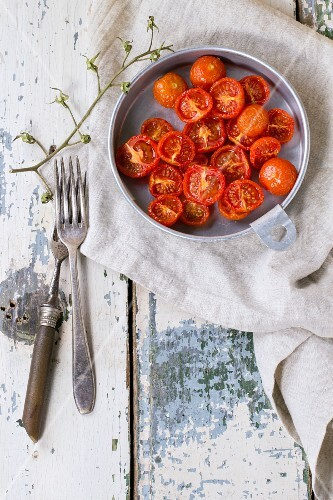 A bowl of baked cherry tomatoes in a bowl on an old wooden table (seen from above)