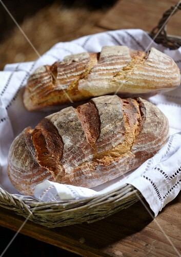 Two rustic loaves of bread in a bread basket on a wooden table