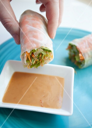 A woman dipping of rice paper roll into a dish of peanut sauce