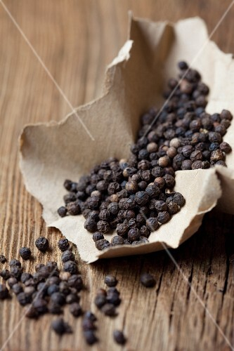 Black peppercorns on a piece of paper