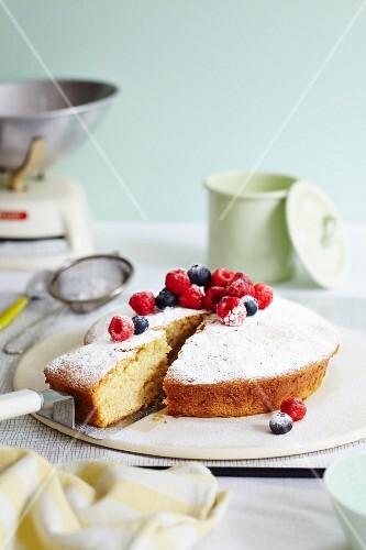 Sponge cake with raspberries, blueberries and icing sugar