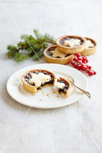 Four mince pies with star lids, one cut open