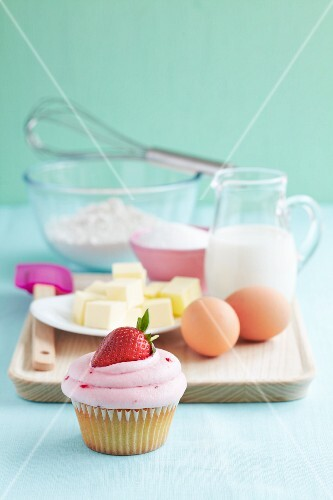 A strawberry cupcake with baking ingredients
