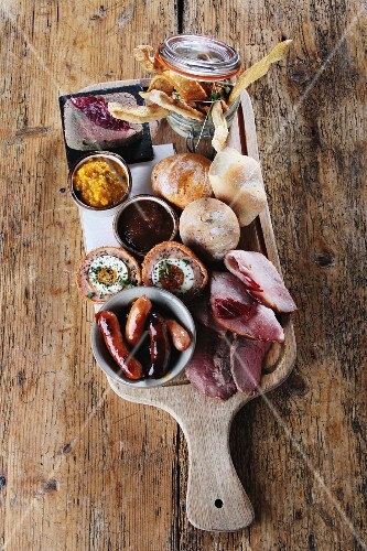 A ploughman's lunch platter of ham, sausages, Scotch eggs, chutney, pickle and bread rolls (England)