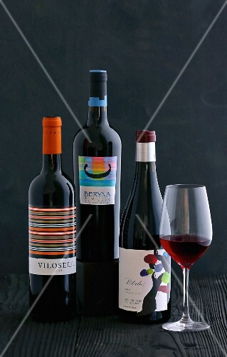 A glass of red wine and three bottles of Spanish red wine