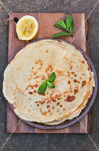 A stack of crepes with a juiced lemon and mint