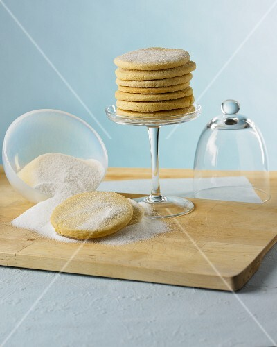 A stack of sugared biscuits on a glass cake stand