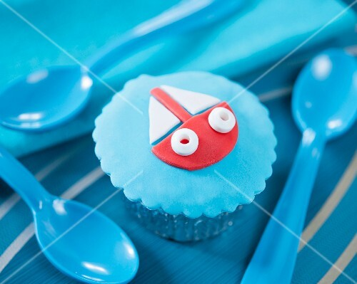A cupcake decorated with a fondant boat on a blue background