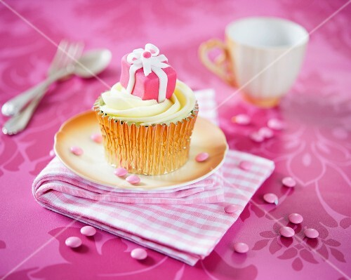 A cupcake decorated with a pink birthday present
