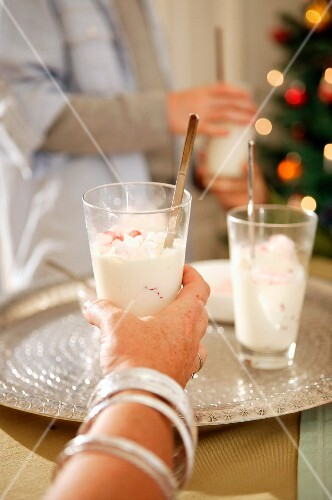 A woman holding a glass of Christmas dessert