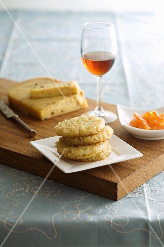 A stack of biscuits, candied oranges and dessert wine