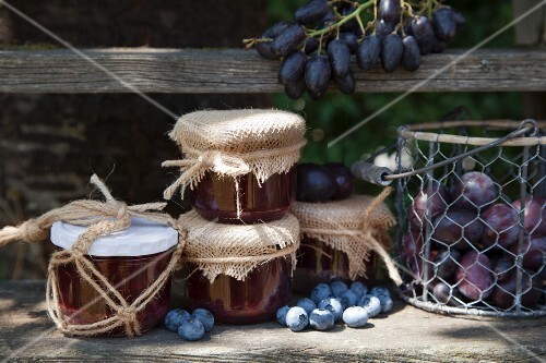 Jam jars with macrame lids and autumn fruits on weathered wooden shelf