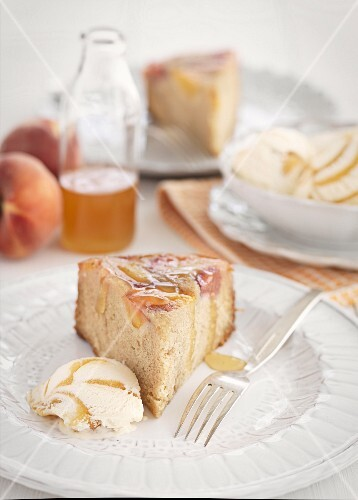 A slice of peach cake with a scoop of ice cream