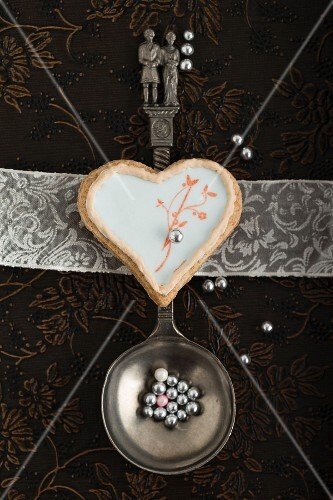 A heart-shaped biscuit with an egg white glaze and a stamped motif on a spoon with a bridal couple