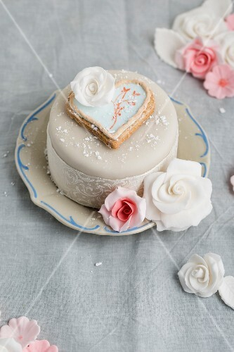 A cake decorated with fondant icing, a heart-shaped biscuit and sugar roses