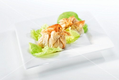 Stuffed filo pastry parcels on lettuce leaves