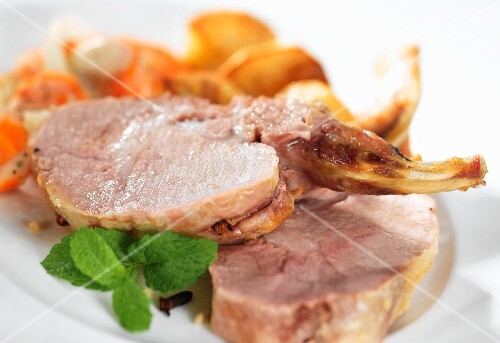 Roast pork chops with a side of vegetables and mint leaves