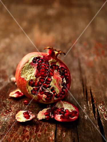 A pomegranate, sliced, on a wooden surface