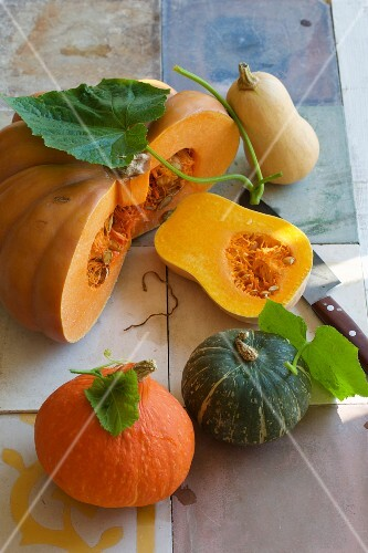 Various types of squash, whole and sliced