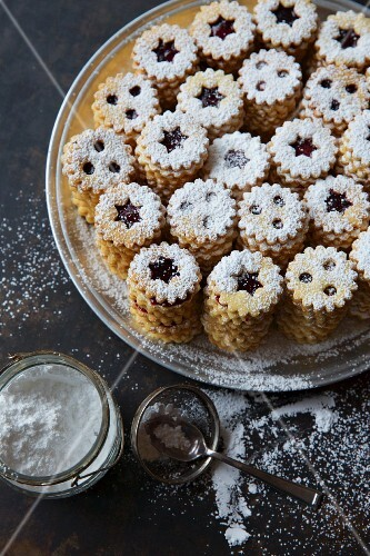 Stacks of jammy shortbread biscuits with icing sugar