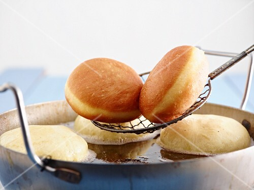 Dougnuts being removed from frying fat