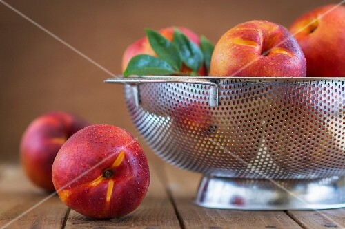 Freshly washed nectarines in a colander on a rustic wooden table