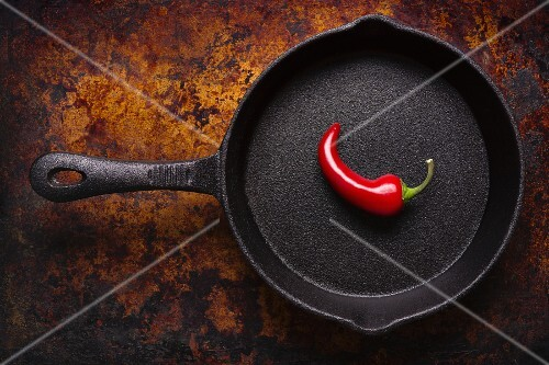 A single red chilli pepper in a cast iron pan (seen from above)