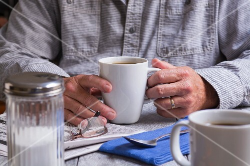 A man holding a cup of coffee and with a newspaper and a pair of glasses next to him