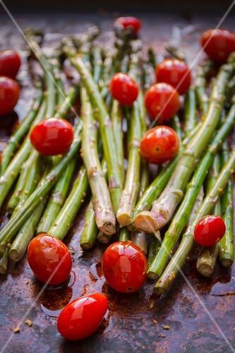 Asparagus and organic grape tomatoes with olive oil and spices on a baking tray