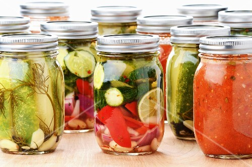 Jars of Mediterranean preserved vegetables: cucumber, courgettes, pepper, onion, lemon and tomato sauce