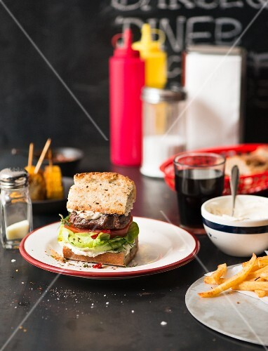 A barbecue burger with chips, mayonnaise and cola in a diner