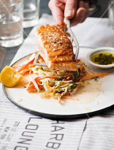Grilled salmon fillet with coleslaw and pesto in a diner