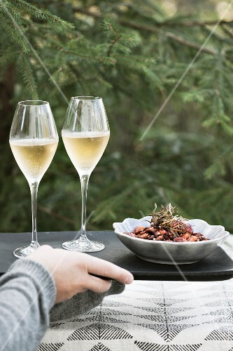 A person outside serving champagne and roasted pecan nuts