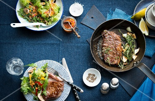 A steak in a pan with a side salad