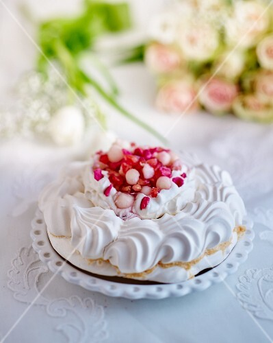 A meringue cake with whipped cream, pink sugared almond and lychees