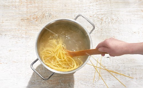 Spaghetti being cooked in a pot with a wooden spoon
