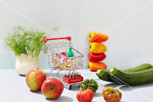 Mini-Einkaufswagen mit Spielzeuglebensmitteln, daneben frisches Gemüse und Obst