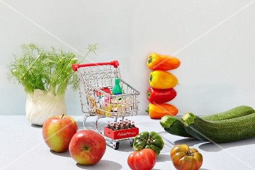 A mini shopping trolley filled with toy foodstuffs next to fresh fruit and vegetables