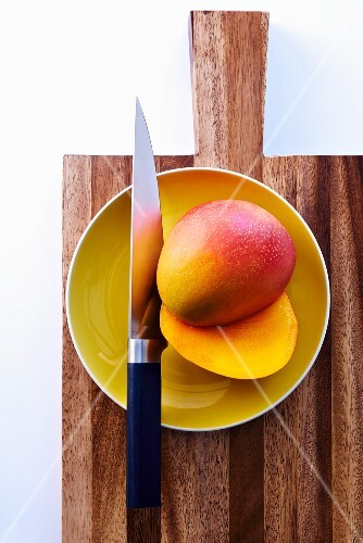 A halved mango on a plate with a knife