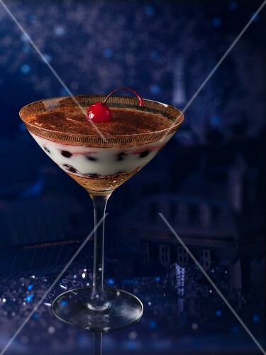 Tiramisu with a cocktail cherry in a stemmed glass