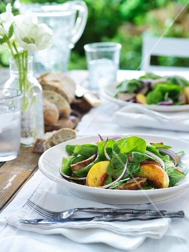 Salad with chipotle pork, young spinach, peach and red onions