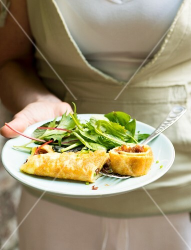 Woman serving omelette with salad in a garden