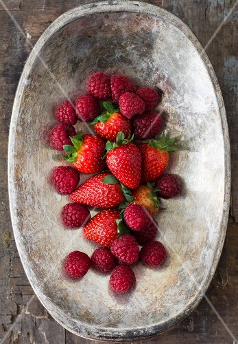 Fresh strawberries and raspberries in a wooden bowl