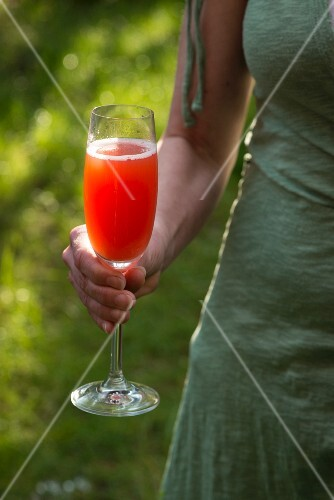 A woman holding a glass of Aperol Spritz
