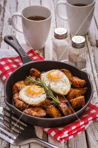 Spiced baked potatoes with fried eggs and rosemary in a cast iron pan
