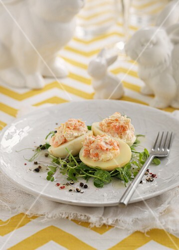 Devilled eggs filled with crab mayonnaise on a bed of cress