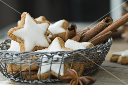 Cinnamon stars and cinnamon sticks in a basket on a rustic wooden table